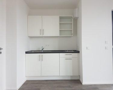 Büroküche Küche In Der Büroküche Steht Eine Kollegin Büro Küche Aufräumen Büroküchenschrank Leichte Büroküche