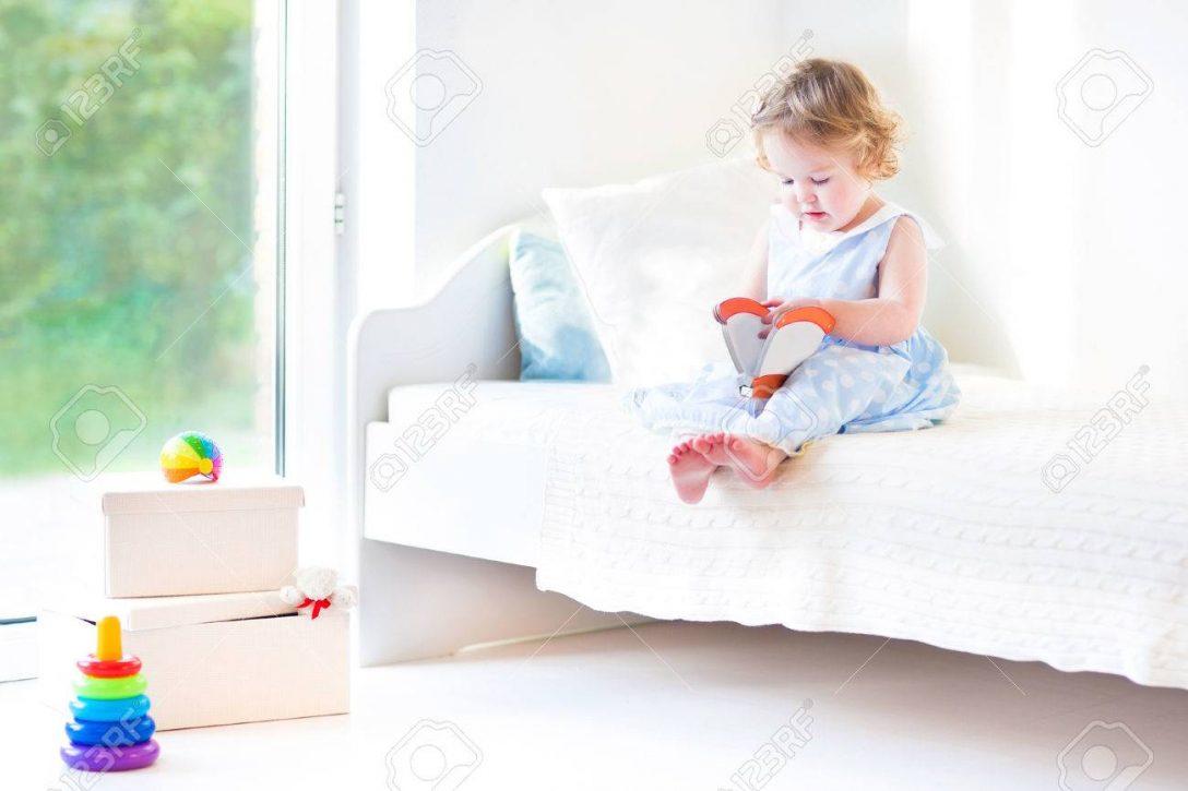 Large Size of Schne Lockige Kleinkind Mdchen Liest Ein Buch Sitzt Auf Einem Betten Kaufen 140x200 Rauch 180x200 120 Bett Breit Ausklappbar Barock 120x200 Mit Stauraum Bett Kleinkind Bett