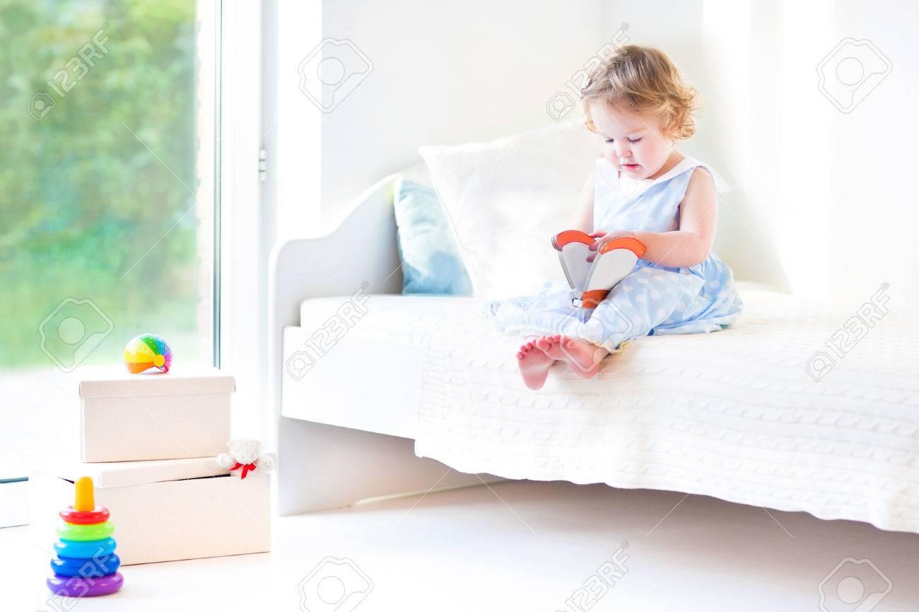 Full Size of Schne Lockige Kleinkind Mdchen Liest Ein Buch Sitzt Auf Einem Betten Kaufen 140x200 Rauch 180x200 120 Bett Breit Ausklappbar Barock 120x200 Mit Stauraum Bett Kleinkind Bett