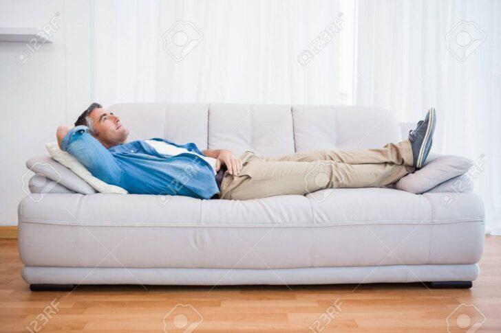 Medium Size of Mann Liegen Und Entspannen Auf Couch Zu Hause Im Fototapeten Wohnzimmer Lampen Teppich Sofa Kleines Wandtattoos Lampe Tapeten Liege Led Komplett Wohnzimmer Liegen Wohnzimmer