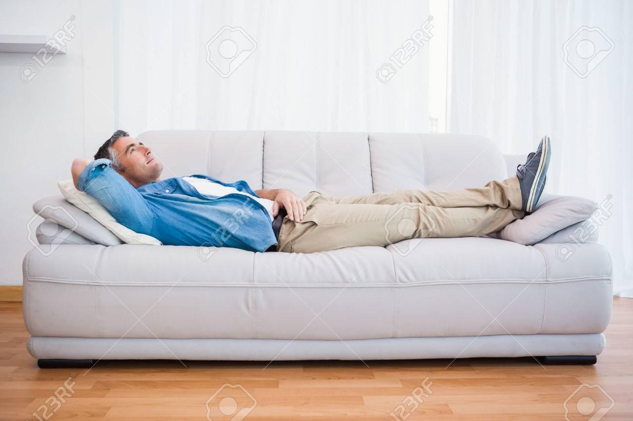Full Size of Mann Liegen Und Entspannen Auf Couch Zu Hause Im Fototapeten Wohnzimmer Lampen Teppich Sofa Kleines Wandtattoos Lampe Tapeten Liege Led Komplett Wohnzimmer Liegen Wohnzimmer