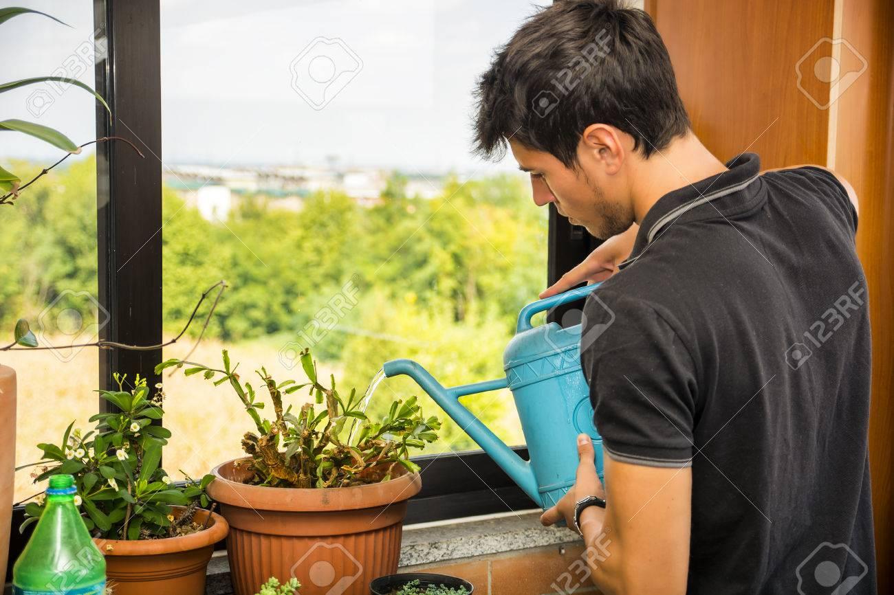 Full Size of Bewässerung Balkon Attraktiver Junger Mann Auf Apartment Mit Bewsserung Von Garten Automatisch Bewässerungssysteme Bewässerungssystem Test Wohnzimmer Bewässerung Balkon